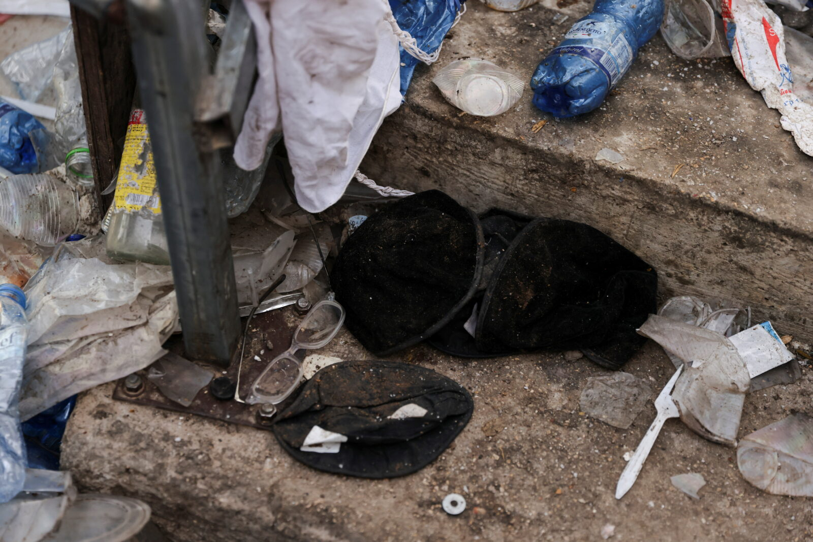 Black yarmulkas seen on stairs with other waste on it as well in Mount Meron