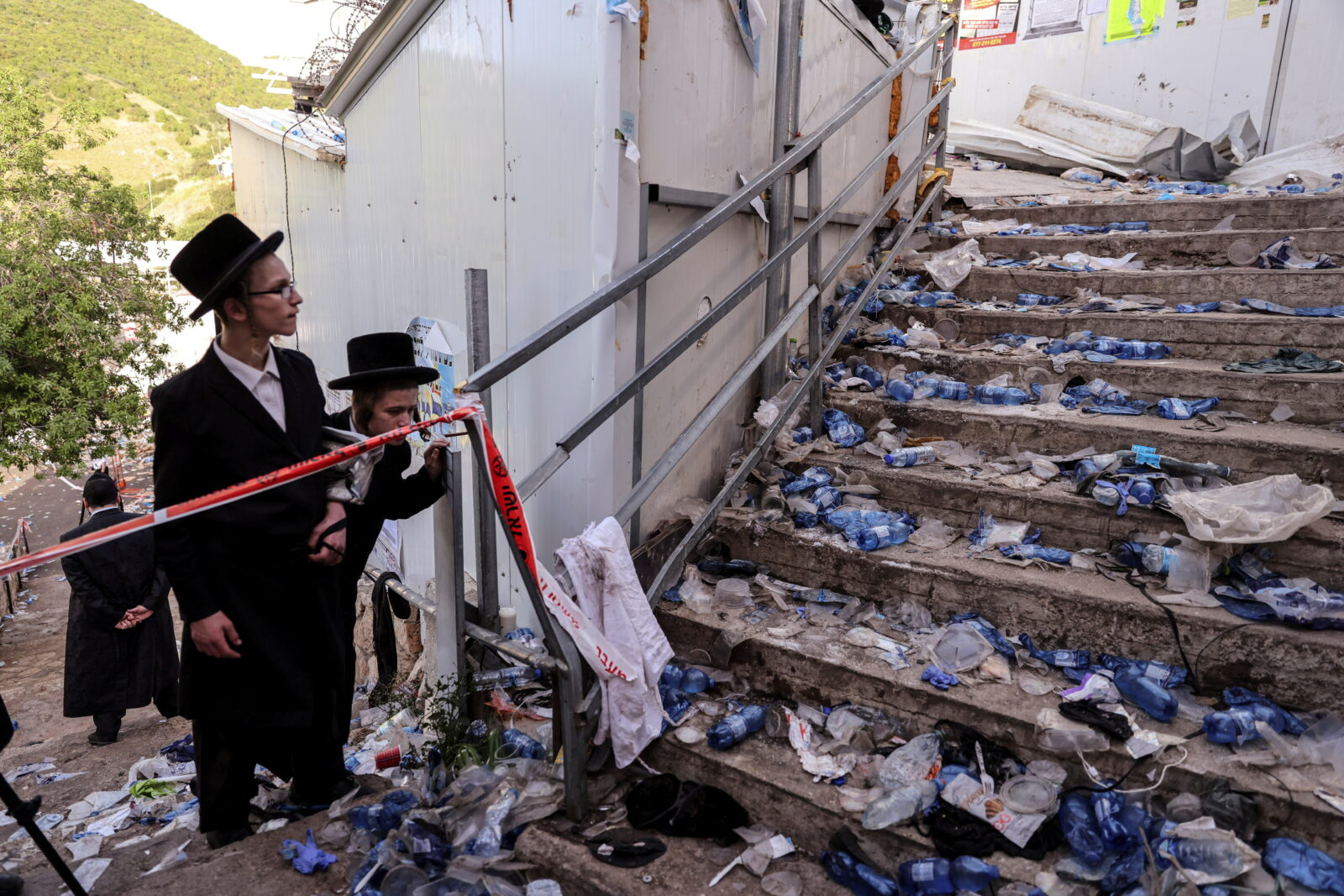 Ultra Orthodox Jews look at stairs with waste on it in Mount Meron